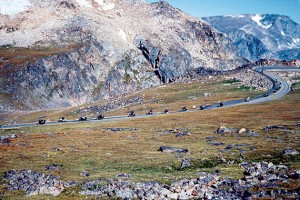 A troop of motorcyclists descends from Beartooth Pass, going west.